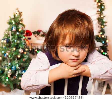 Sad kid sitting with Christmas tree and fire place on the background sad as Christmas is over - stock photo