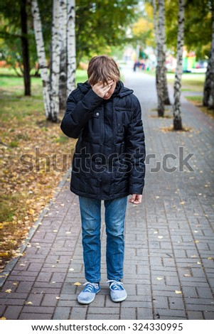 Sad Kid stand in the Autumn Park