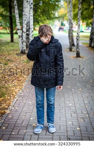Sad Kid stand in the Autumn Park - stock photo