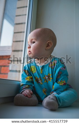 Sad kid with ball sitting near window  and looking outside - stock photo