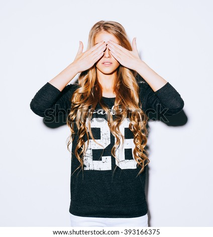 Sad lifestyle portrait beautiful blond girl closes eyes with her hands, in Sweatshirt and white shorts. Indoor. Warm color. Hipster. - stock photo