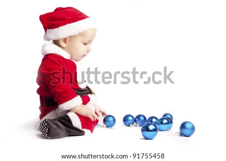 sad little baby boy Santa sits and stares at the blue Christmas balls on white background put his hands on his knees - stock photo