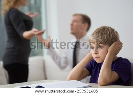 Sad little boy and family fight in living room - stock photo