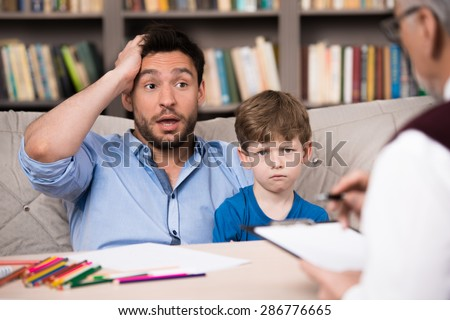 Sad little boy and his uptight father talking with psychologist. Psychologist taking notes. There are many books in psychologist office - stock photo