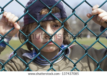 sad little boy behind a fence - stock photo