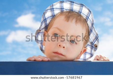 sad  little boy in hat looking away on sky background - stock photo