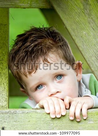 sad little boy inside a wooden frame - stock photo