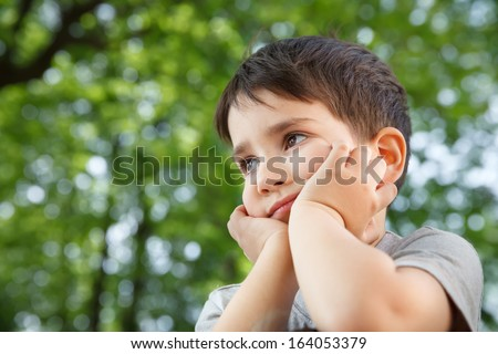Sad little boy looking at something against blurred natural background