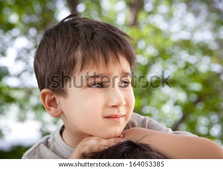 Sad little boy looking at something against blurred natural background - stock photo
