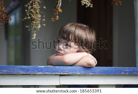 sad little boy on the porch of rural house - stock photo