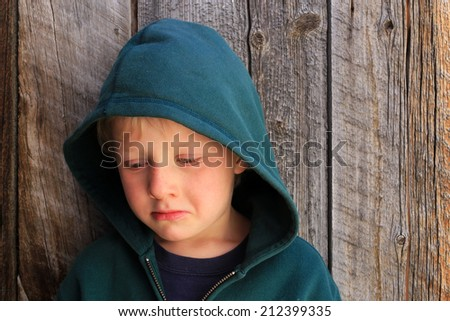 Sad little boy pouting with a rustic wood background. - stock photo
