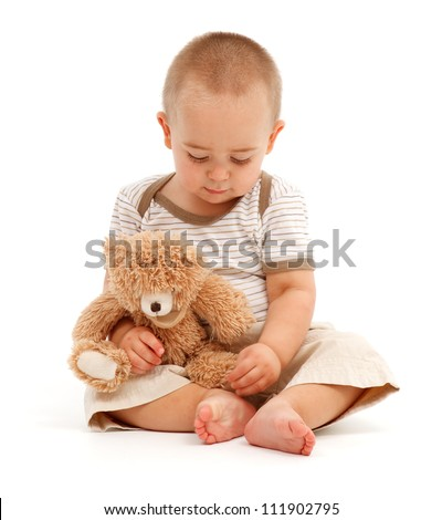 Sad little boy sitting and playing with his toy bear - stock photo