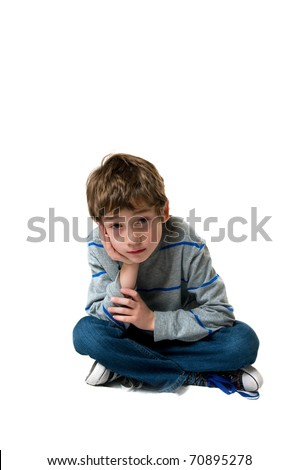 sad little boy sitting cross legged on the floor studio shot isolated on white