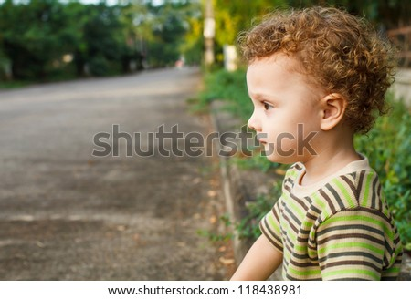 sad little boy sitting near the road - stock photo