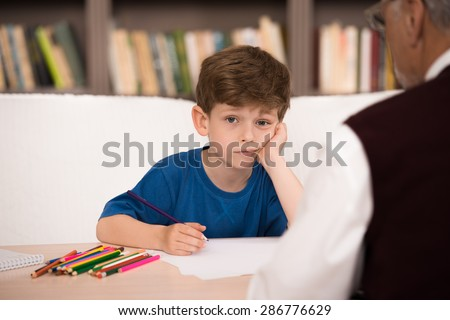Sad little boy trying to draw in psychologist office. Focus on boy. There are many books in psychologist office - stock photo