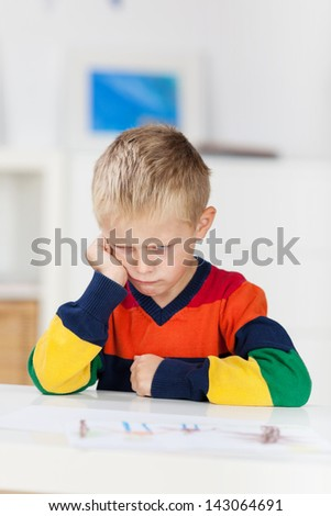 Sad little boy with drawing on table in house - stock photo