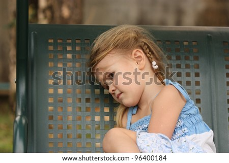 sad little child on a bench - stock photo