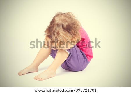 sad little girl covered her face sitting - stock photo