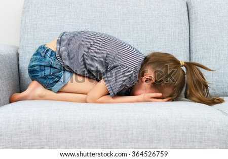 Sad little girl crying on the sofa. - stock photo