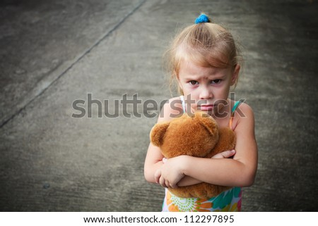 sad little girl holding toy with her hands - stock photo