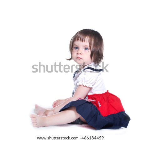 Sad little girl in a colorful dress. Isolated on white background