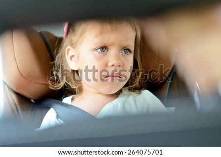 sad little girl in the car seat - stock photo