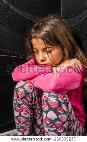 Sad little girl is sitting in the corner of the room - stock photo