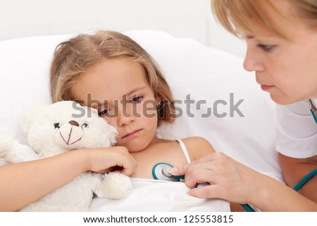 Sad little girl laying sick in bed checked by a doctor - stock photo