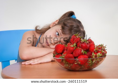 sad little girl looks at a plate of strawberries