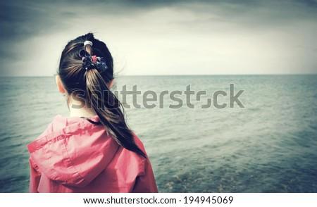Sad little girl looks at the sea - stock photo