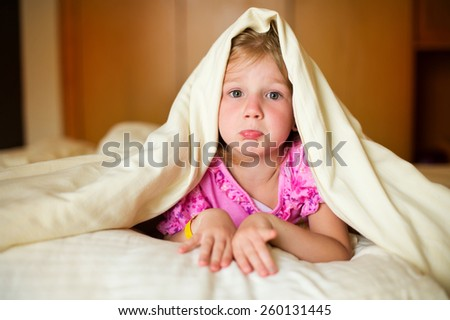 Sad little girl lying on bed under blanket and posing in room of her flat - stock photo