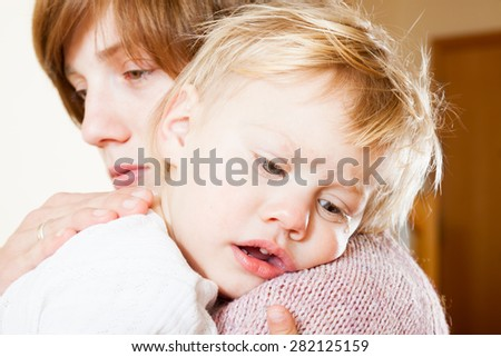 Sad little girl on hands at mum - stock photo