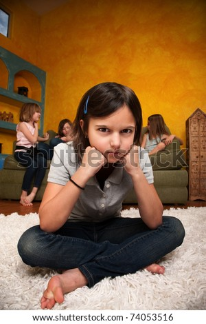 Sad little girl sits away from her friends - stock photo