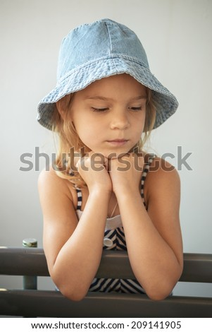 Sad little girl sits on bench. - stock photo