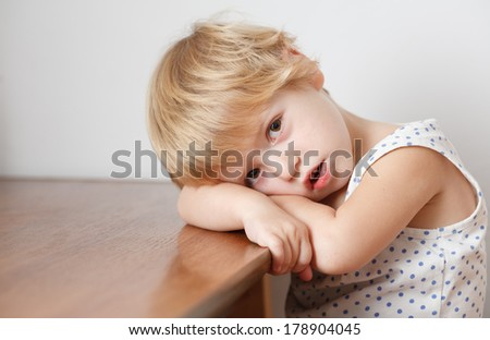 Sad little girl sitting at the table crying looking at camera stock