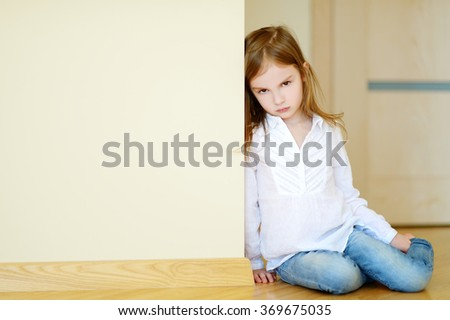 Sad little girl sitting on a floor at home - stock photo