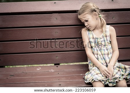 sad little girl sitting on bench in the park at the day time - stock photo