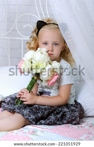 Sad little girl sitting on the bed with flowers in their hands - stock photo