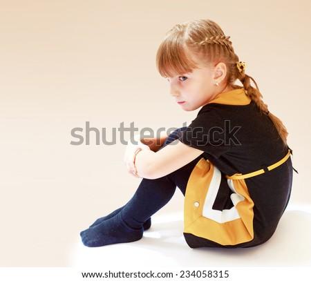 sad little girl sitting on the floor covering knees - stock photo