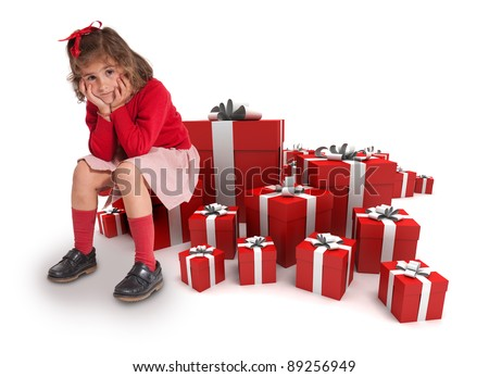 Sad little girl sitting surrounded by gift boxes - stock photo