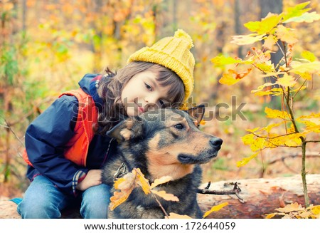 Sad little girl with big dog in the forest in autumn - stock photo