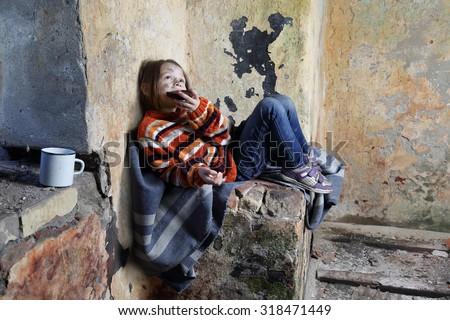 Sad little girl with dirty face sits on old blanket in basement and eats rough black bread - refugee orphan, hunger concept - stock photo
