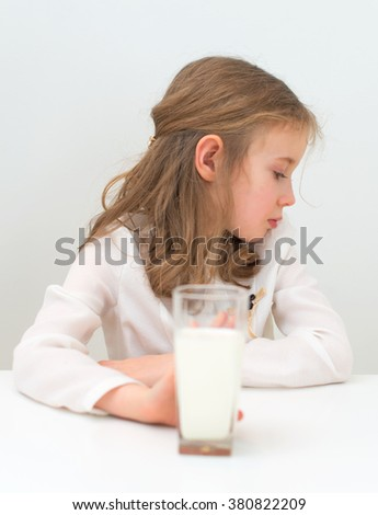 Sad little girl with glass of milk. - stock photo