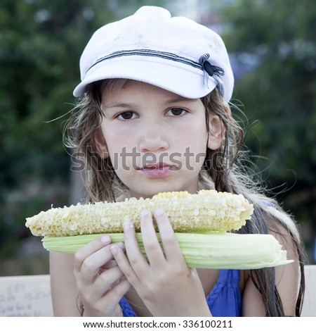 sad little girl with maize looking at camera - stock photo