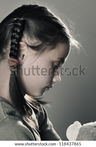 Sad little girl with toy on grey background closeup - stock photo