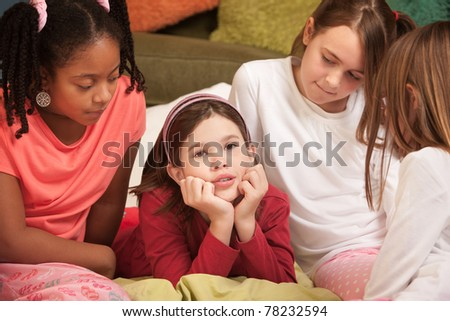 Sad little with hands on chin with friends at a sleepover - stock photo