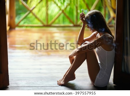Sad lonely beautiful woman smoking cigarette and sitting on the porch during the rain - stock photo