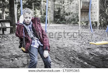 sad lonely boy sitting on swing - stock photo
