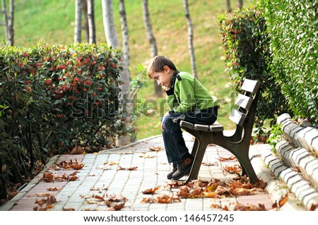sad lonely child in the park - stock photo