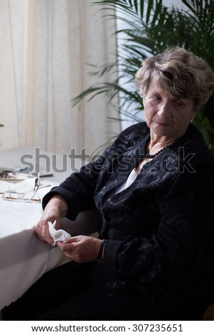 Sad lonely senior woman in black clothes - stock photo